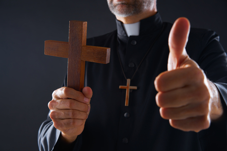 Priest holding cross of wood praying with ok sign finger Stock Photo