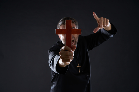 Priest holding cross of wood praying in foreground