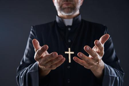 Ksiądz otwiera ręce, ramiona modląc się, ofiarowując ofiarę