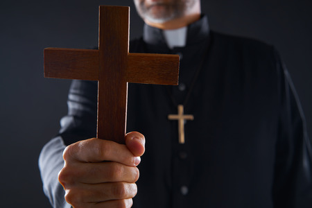 Priest holding cross of wood praying in foreground Stock Photo - 110852457