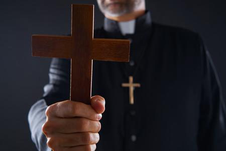 Sacerdote sosteniendo la cruz de madera orando en primer plano Foto de archivo