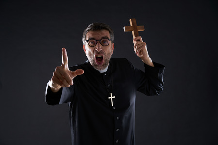 Priest holding cross of wood praying and shouting Stock Photo