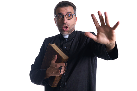 Priest scared shounting raising hand on white background Banco de Imagens