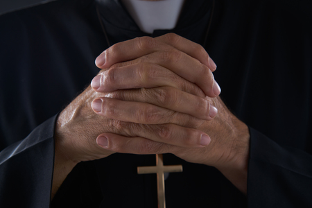 Praying hands priest portrait of male pastor