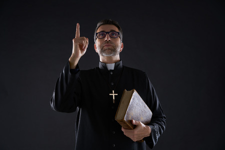 Priest male holding bible pointing finger up to heaven in sky