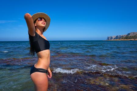 Bikini girl in summer Mediterranean beach having fun with beach hat
