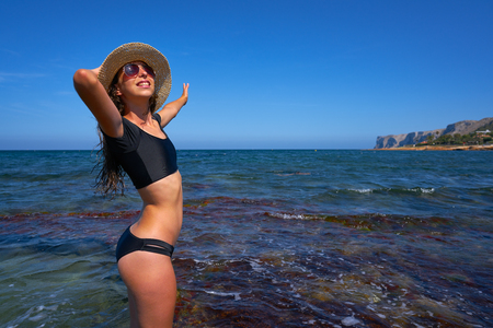Bikini girl in summer Mediterranean beach having fun with beach hat