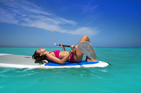 Girl relaxed lying on paddle surf board SUP relaxed in summer Stock Photo