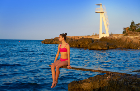 Girl at beach sunset on trampoline springboard
