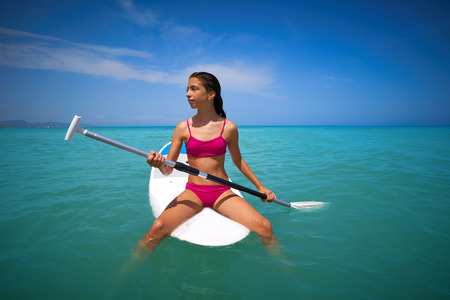 Girl relaxed sitting on paddle surf board SUP in summer