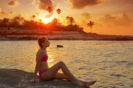 Girl silhouette at beach sunset relaxed sitting