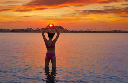 Girl silhouette at sunset heart shape in hands fingers on the beach
