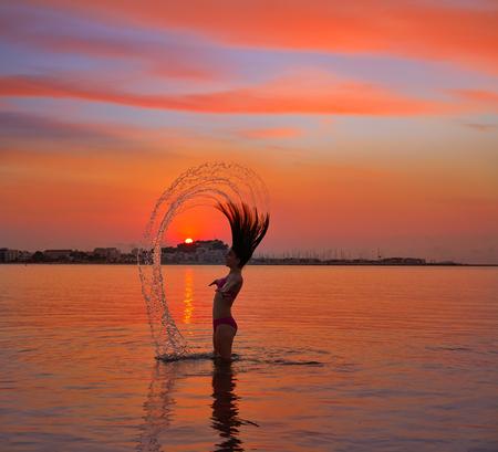 Girl flipping hair flip at sunset beach in orange sky