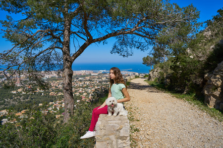 Girl wirh pet dog looking at Denia aerial view in alicante of Spain
