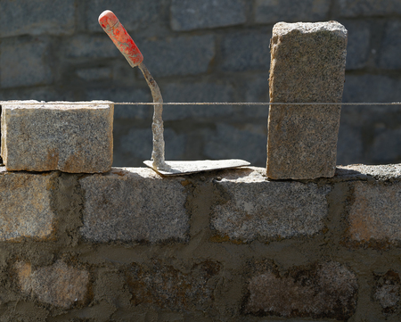 Granite blocks wall construction with cement mortar and trowel tool Stock Photo