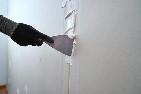 Laminierte Gipskartonplatten verputzen Detailspachtel und Hand