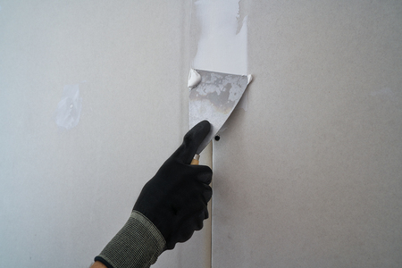 Laminated plasterboard plastering join detail spatula and hand Stock fotó