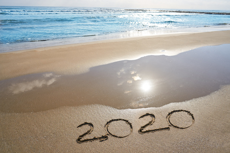 year 2020 numbers spell written on beach sand shore Stock Photo