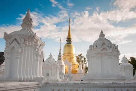The golden pagoda in Wat Suan Dok, Chiangmai, Thailand contrasted with beutiful blue sky and clouds  photo