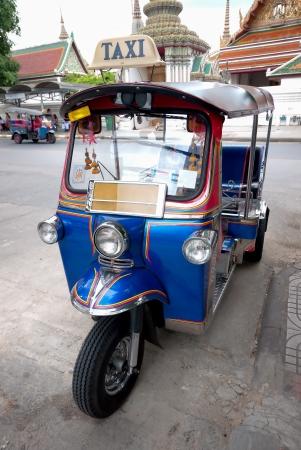 Tuktuk on street with temple background in Bangkok photo