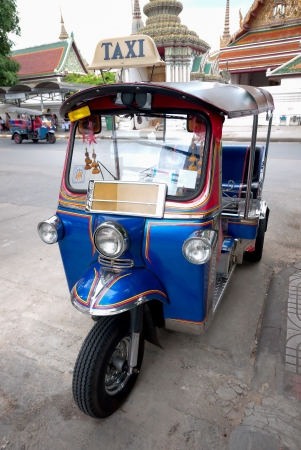 tuktuk: Tuktuk on street with temple background in Bangkok