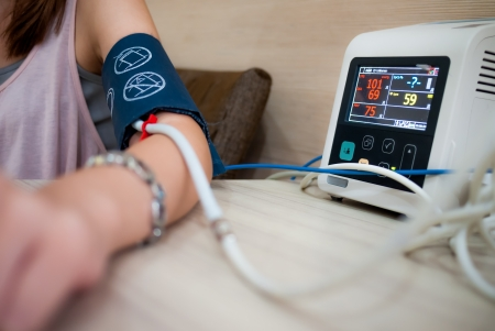 medical physician: Measuring female blood pressure in a hospital Stock Photo