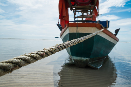 Boat rope to anchor on the beach photo