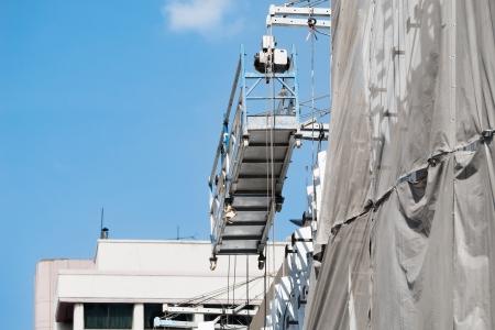 Empty hanging scaffold under blue sky Фото со стока