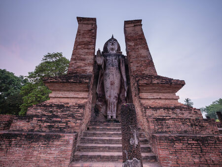 Standing ancient Sukhothai Buddha at dusk, Thailand