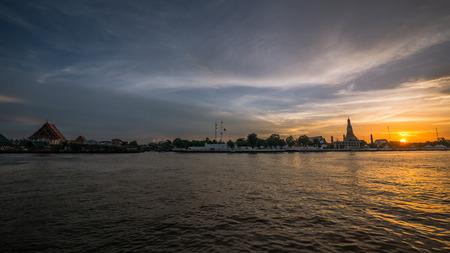 Chao Praya river (Bangkok, Thailand) at golden hour with Wat Arun and Wat Kalayanamitr in the background. Фото со стока