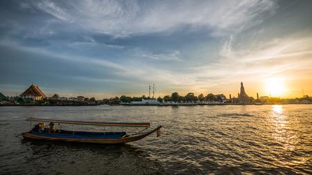 praya: Chao Praya river and a moving boats (Bangkok, Thailand) at golden hour with Wat Arun and Wat Kalayanamitr in the background.