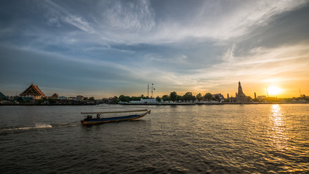 Chao Praya river and a moving boats (Bangkok, Thailand) at golden hour with Wat Arun and Wat Kalayanamitr in the background.