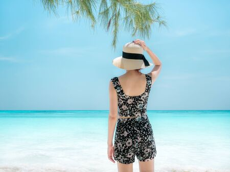 The back of a young girl looking to the sea