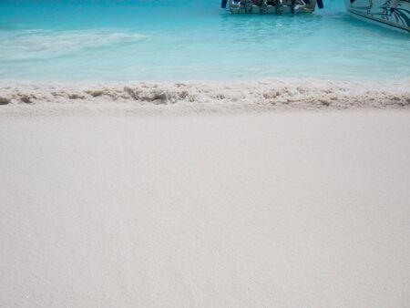 Wave splashing white sand on a white beach