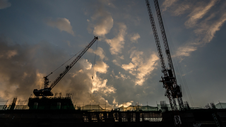 Silhouette of a building under Construction at sunset Фото со стока