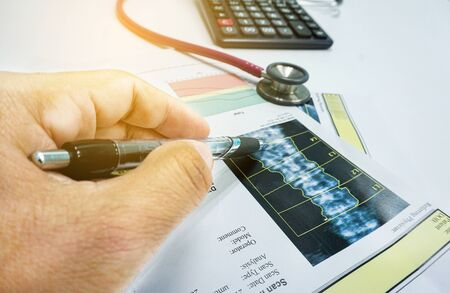 Closeup Artificial intelligence in smart healthcare hospital technology concept. Doctor point pen to bone density screen and machine learning detect in X-Rays process.