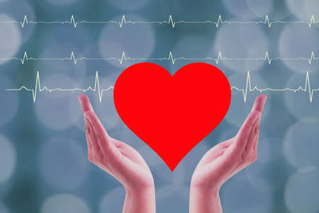 Close up Hands woman Holding and save Heart donor Icon Isolated On wave ekg and blurry background