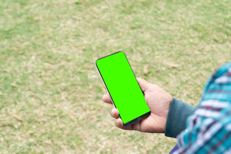 Hand holding phone with the green color in front of a floor background,Smartphone in hand with a green chromakey screen.