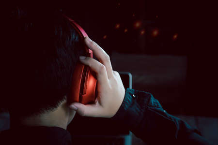 Portrait from behind and back views of a human wearing headphones orang to listen to music after working background Фото со стока