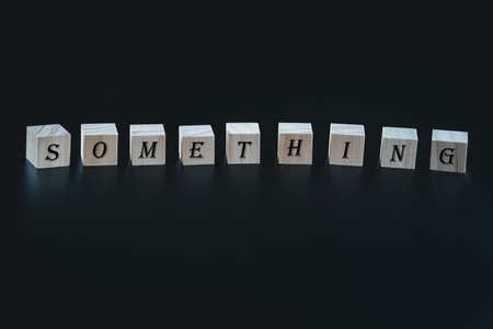 Wooden blocks symbol with words 'something ' on beautiful black background. Business, time for something new concept.