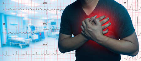 Close Up Men have chest pain caused by heart disease, heart attack, heart leakage, coronary heart disease on Electrocardiogram graph and blurry Emergency room background