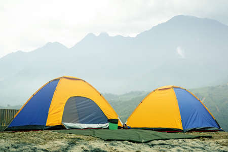 Tourist dome tent camping  in forest camping  The fog covered the mountains in the morning.on mountain background