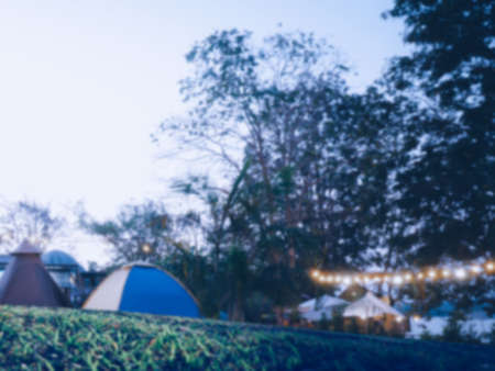 Blured image of camping and tent with high iso grained picture,with field tents group in camping area at natural parkland.