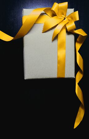 isolated on yellow: Vintage gift with yellow gold bow on black wooden background Stock Photo