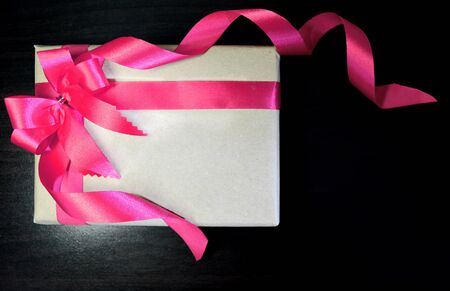 lazo rosa: Vintage gift with  pink bow on black wooden background
