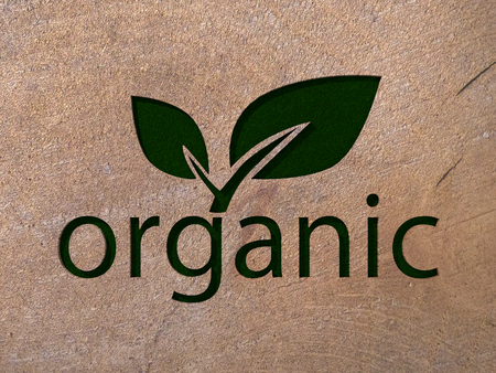 Organic text with a leaf on wood