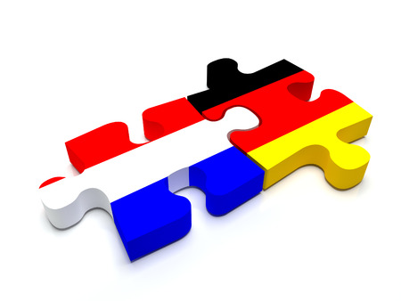 Puzzle pieces connect a piece containing the dutch flag and the german flag. Standard-Bild
