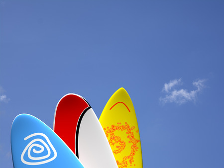A set of surf boards vertically positioned with a blue sky and some clouds on the background