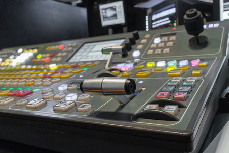 switcher: Wide shot of vision mixing panel in a television gallery.