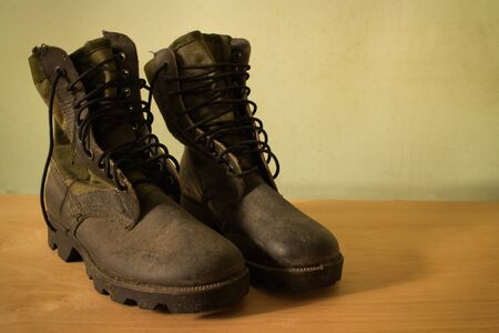 military boots: Old jungle boot still life on wood background